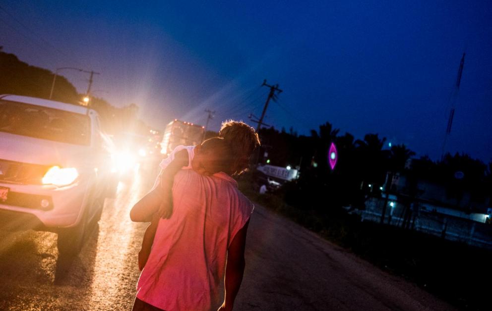 Luis Martínez, de 29 años, carga a su hijo Fernando Martínez, de uno, mientras pide limosna en el municipio de Matías Romero, Oaxaca. Ellos son salvadoreños que decidieron unirse a la caravana migrante debido a que en dos ocasiones los pandilleros le quitaron la mercadería que vendían en el occidente de El Salvador, lo que provocó su huida.
