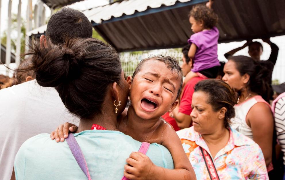 Viernes 19 de octubre. La mayor parte de la caravana de migrantes permaneció, al menos durante seis horas, bajo el intenso calor de la frontera de Tecún Umán, ante la imposibilidad de cruzar la frontera mexicana. En la fotografía, un niño, que se había desmayado sobre el hombro de su madre, recobra el conocimiento tras haber sido reanimado con un baño de agua fría (Fuente: Fred Ramos, El Faro).