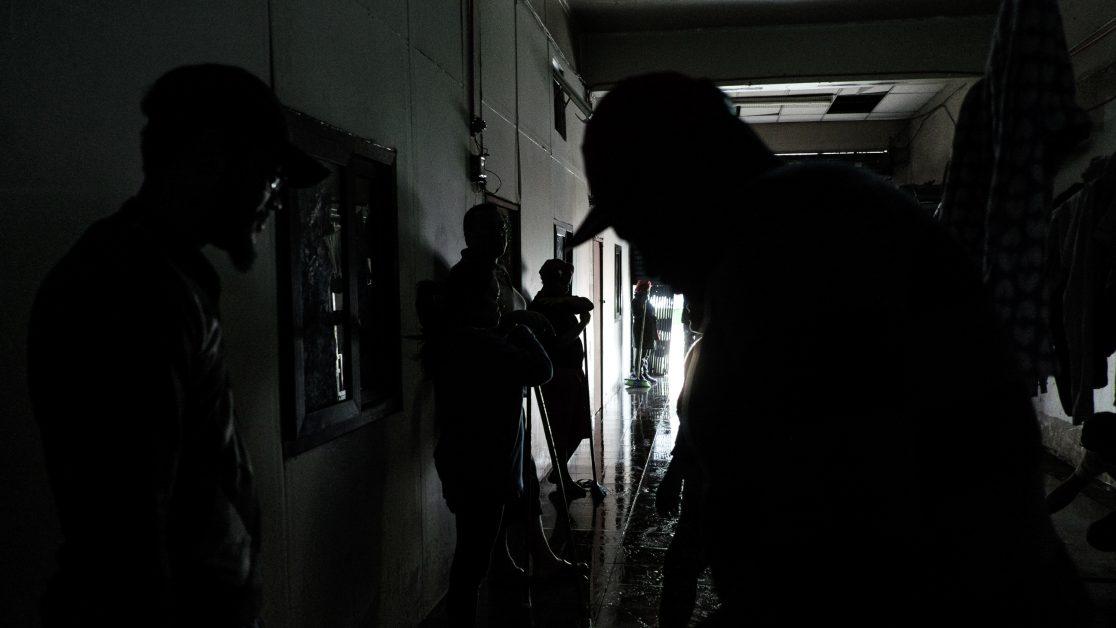 Los vecinos se organizan para limpiar el ingreso a uno de los galpones donde se ubican sus habitaciones, lugar que ocupan además para tender ropa y guardar sus implementos de trabajo. Foto: Jorge Vargas | Migrar Photo