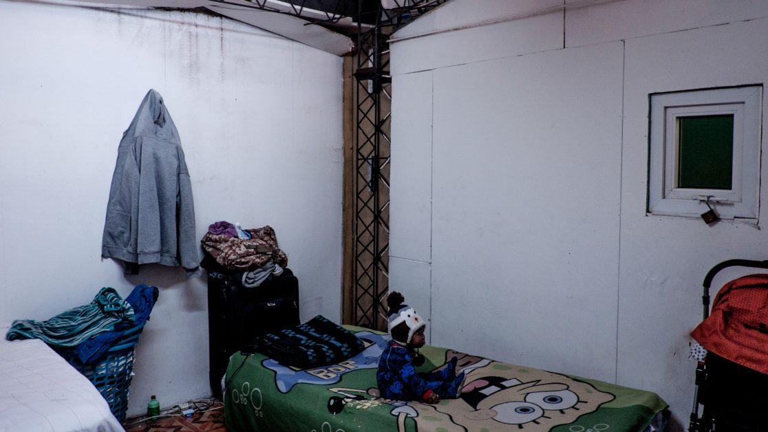 Un niño está sentado en una de las tres camas que hay en su habitación, que mide 12 metros cuadrado y que comparte con otras familias de origen haitiano. Foto: Jorge Vargas | Migrar Photo