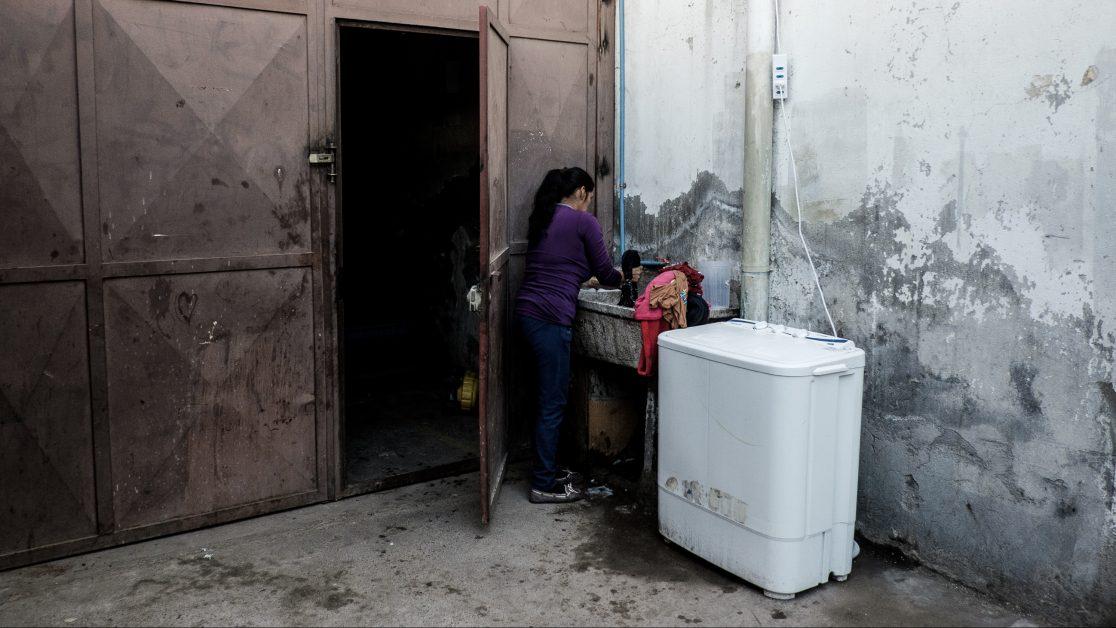 Una mujer, de origen peruano, lava su ropa en el único lugar con luz natural del galpón. Foto: Jorge Vargas | Migrar Photo